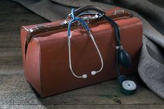 Medical bag and pressure meter on the wooden table Stock Photography