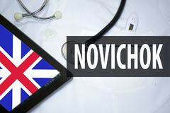 Medical bathrobe, tablet with English flag and inscription with Russian in Latin transcription - `Novichok`. News concept