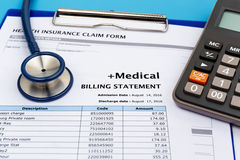 Medical bill with calculator. Medical cost concept with calculator and stethoscope Royalty Free Stock Images