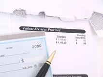 A medical bill and check book. A medical concept with a statement bill and checkbook Stock Images