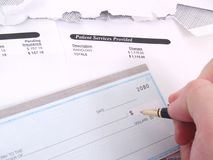 A medical bill and check book. A medical concept with a statement bill and checkbook Royalty Free Stock Images