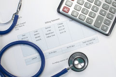 Medical Bill. Health care billing statement with stethoscope and calculator. Medical bill is fictitious royalty free stock image