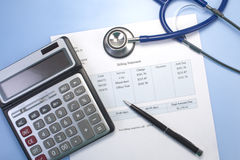 Medical Bill. Health care billing statement with stethoscope, pen and calculator. Medical bill is fictitious royalty free stock images