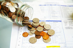 Medical bill pay. Coin jar with money on medical bills Stock Photography