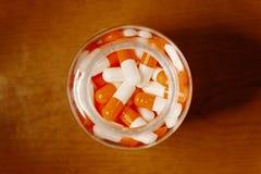 Medical Bottle Full Of Orange-white Pills Stock Image