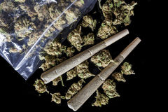 Medical cannabis joints and buds scattered from package black above Stock Photo