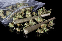 Medical cannabis joints and buds scattered from package black side Royalty Free Stock Image