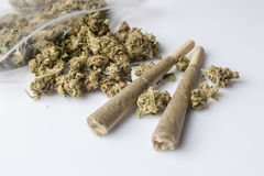 Medical cannabis joints and buds scattered from package white side Stock Photography