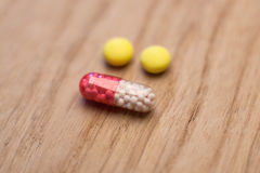 Medical capsule and two yellow pills Royalty Free Stock Images