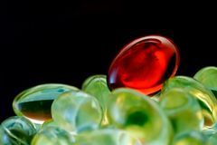 Medical capsules. Red vitamin dragee on a heap of medical capsules Stock Image