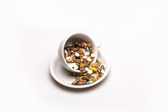 Medical capsules and tablets inside coffee cup Stock Photo