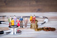 Medical care and expenses, health insurance. Colorful Human miniatures.  Royalty Free Stock Image