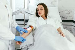 Medical Center. Doctor Scanning Woman Hand With Vein Finder royalty free stock photos