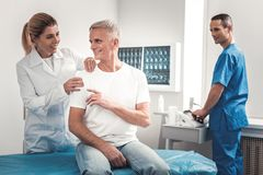 Grey-haired man feeling secure during medical checkup. Medical checkup. Grey-haired retired men feeling rather secure during medical checkup at the chiropractor royalty free stock images