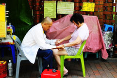 Medical Chi Kung therapy. Picture of an oriental doctor practicing medical chi kung (qigong) therapy like faith healing to his ailing patient in a sidewalk in Royalty Free Stock Photos