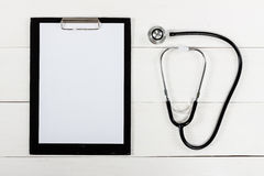 Medical clipboard and stethoscope on white wooden table Royalty Free Stock Image