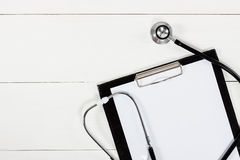 Medical clipboard and stethoscope on white wooden table Royalty Free Stock Images