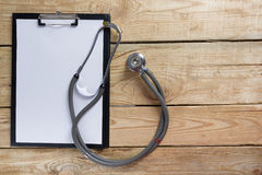 Medical clipboard and stethoscope on wooden desk background. Top view. Workplace of a doctor. Royalty Free Stock Photo