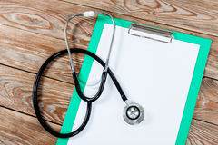 Medical clipboard and stethoscope on wooden table background. Stock Photography