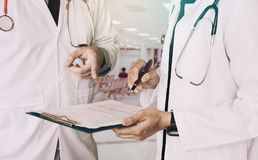 Medical colleagues holding clipboard with paper and working toge Stock Images