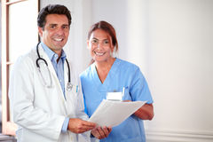 Medical colleagues looking and smiling at you. Portrait of a medical colleagues looking and smiling at you while holding documents - copyspace royalty free stock photo