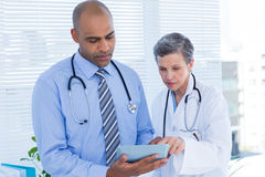 Medical colleagues working with tablet computer Stock Image