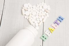 Color HEALTH  inscription and white heart of pills and capsules on white wooden desk Stock Photography
