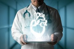 Doctor showing heart hologram from computer. Medical Concept - Doctor showing heart hologram generated from tablet computer royalty free stock photography