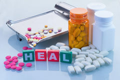 Medical concept with heal text and pills with bottles background Stock Photos