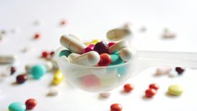 Medical concept. Slow motion of medicine pills drops into overcrowded plastic spoon stock video footage