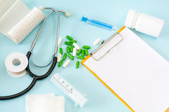 Medical conceptual picture with a stethoscope, pills, injection, gauze, adhesive plaster, bottle, empty clipboard sheet. Royalty Free Stock Image
