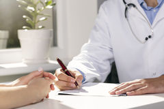 Medical consultation - doctor and patient sitting by the table. And writing document royalty free stock image