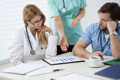 Medical consultation in progress. Three doctors in doctors room during medical consultation Royalty Free Stock Images