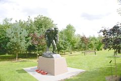 Medical Corps Memorial. Memorial dedicated to the work of the royal army medical corps with medic carrying injured man on plinth. This life size memorial is Royalty Free Stock Photo