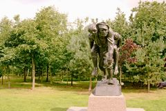 Medical Corps Memorial. Memorial dedicated to the work of the royal army medical corps with medic carrying injured man on plinth. This life size memorial is Stock Photo