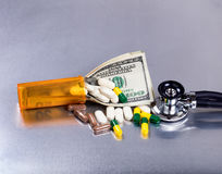 Medical cost concept with money and medicine on stainless steel Royalty Free Stock Photo