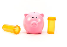 Medical Costs. Pink piggy bank with two empty prescription medicine bottles on white background stock photography