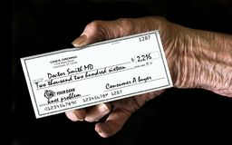Medical costs that burden elderly citizens is represented here with an elderly hand holding a large generic, mock check made out royalty free stock images