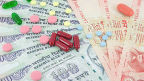 Medical Costs. Pills, capsules and tablets on Indian rupees, highlighting medical costs Stock Images