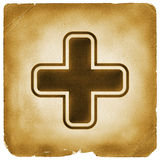 Medical cross symbol on old paper. First aid cross sign, health point, life station, healthcare or survival pack icon on weathered papyrus Stock Photography