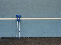 Medical crutch at blue training tennis wall  on outdoor stadium players court, Stock Images