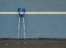 Medical crutch at blue training tennis wall  on outdoor stadium players court, Stock Photography