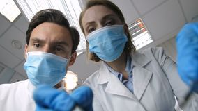 Medical dental staff treating patient low angle. Medical dental staff in white lab coats, face masks and gloves treating patient at clinic, low angle, patient stock footage