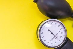 Medical device sphygmomanometer for checking and measuring of blood pressure on yellow uniform background view from above with cle royalty free stock image