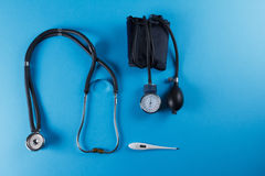 Medical devices stethoscope, tonometer, and thermometer. On blue background. Copyspace stock photo