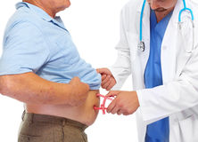 Medical doctor with body fat calipers. Doctor measuring obese man stomach with body fat calipers Stock Photos