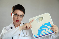 Medical doctor with body scales. Weight problem. Stock Photography