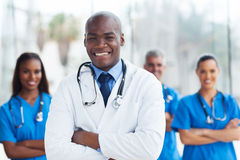 Medical doctor colleagues. Handsome african american medical doctor with colleagues in background Royalty Free Stock Images
