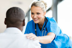 Medical doctor comforting pateint. Caring medical doctor comforting patient in office stock photos