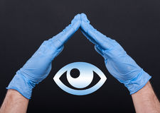 Medical doctor with eye symbol between hands. As ophtalmology concept  on black background Royalty Free Stock Photos